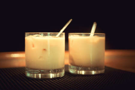 Preparation of white russian cocktails on the bar counter on rubber mat. Shallow DOF and marsala tonned Standard-Bild