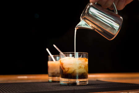 Preparation of white russian cocktails on the bar counter on rubber mat. Shallow DOF and marsala tonned 免版税图像