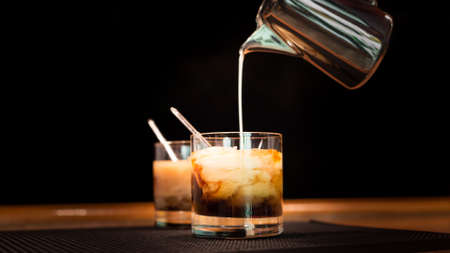 white  russian: Preparation of white russian cocktails on the bar counter on rubber mat. Shallow DOF and marsala tonned Stock Photo