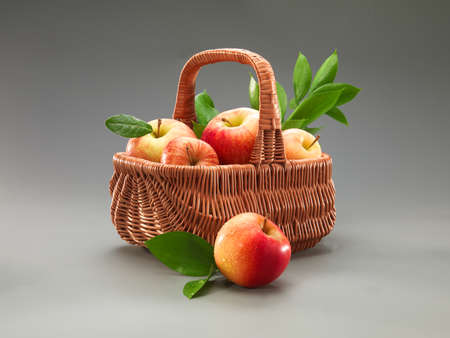 Basket of red apples on the grey background