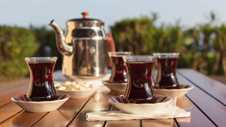 traditional culture: Turkish tea with teapot and locum in outdoor cafe. Direct sunset light. Shallow DOF and lightly toned Stock Photo