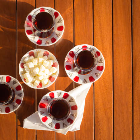 locum: Top view of turkish tea with locum in outdoor cafe. Direct sunset light. Shallow DOF and lightly toned Stock Photo