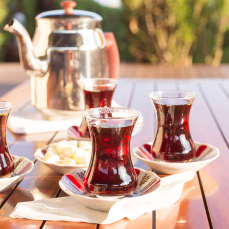 Turkish tea with teapot and locum in outdoor cafe. Direct sunset light. Shallow DOF and lightly toned Imagens