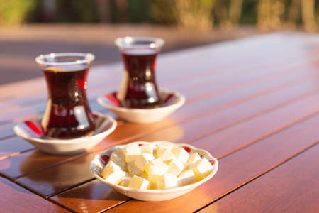 Locum and turkish tea in outdoor cafe. Direct sunset light. Shallow DOF and lightly toned