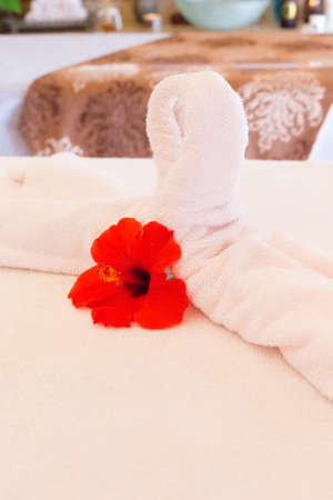 swimming candles: Towel decoration on massage table. Spa interior. Shallow DOF