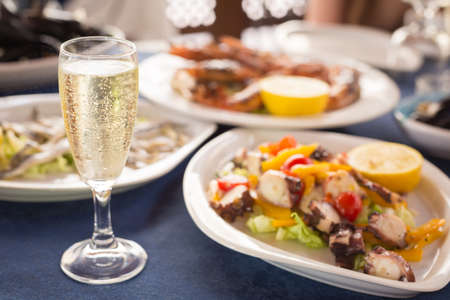 Italian cuisine. Glass of prosecco and variety of seafood. Shallow DOF, horizontal