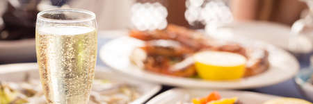 Italian cuisine. Glass of prosecco and variety of seafood. Shallow DOF, banner
