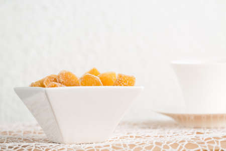 crystallized: Crystallized ginger root  in white porcelain bowl and cup of tea on the background. Cup is cut. Shallow DOF. Close-up photo, horizontal Stock Photo