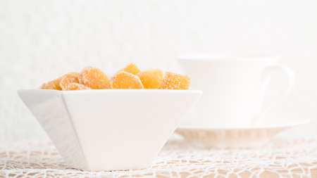 crystallized: Crystallized ginger root  in white porcelain bowl and cup of tea on the background. Shallow DOF. Close-up photo, horizontal