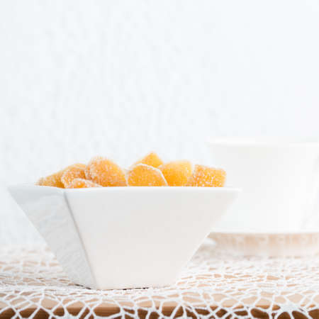 crystallized: Crystallized ginger root  in white porcelain bowl and cup of tea on the background. Shallow DOF. Close-up photo, square Stock Photo