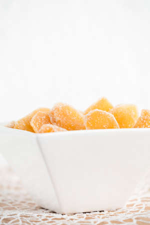 Crystallized ginger root  in white porcelain bowl. Bowl is cut vertically. Shallow DOF. Close-up photo, vertical Imagens