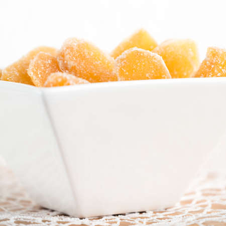 square root: Crystallized ginger root  in white porcelain bowl. Bowl is cut vertically. Shallow DOF. Close-up photo, square Stock Photo