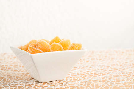 crystallized: Crystallized ginger root  in white porcelain bowl on white tablecloth. Shallow DOF. Close-up photo, horizontal