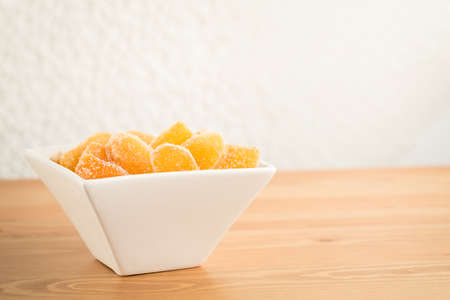 crystallized: Crystallized ginger root  in white porcelain bowl on wooden background. Shallow DOF. Close-up photo, horizontal