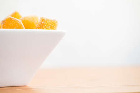 Crystallized ginger root  in white porcelain bowl. Bowl is cut vertically. Shallow DOF. Close-up photo, horizontal, copy space