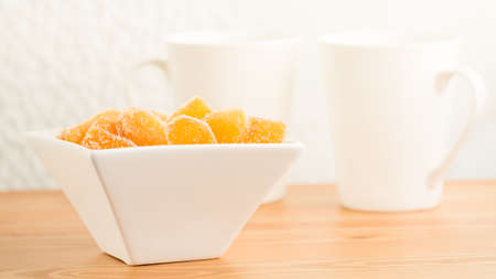 crystallized: Crystallized ginger root  in white porcelain bowl and two tea mugs on the wooden background. Shallow DOF. Close-up photo, horizontal Stock Photo