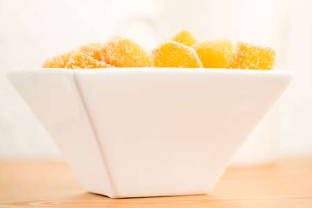 Crystallized ginger root  in white porcelain bowl. Shallow DOF. Close-up photo, horizontal, warm tone