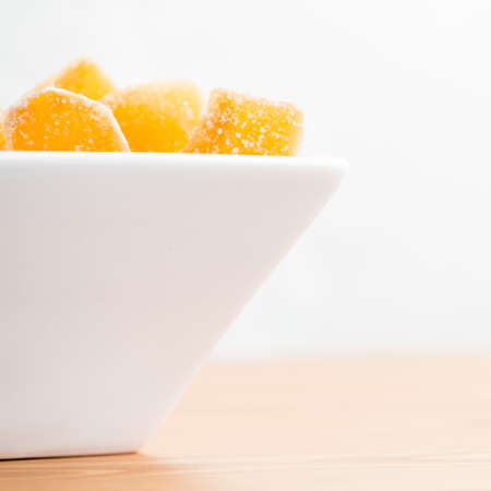 crystallized: Crystallized ginger root  in white porcelain bowl. Bowl is cut vertically. Shallow DOF. Close-up photo, square, copy space