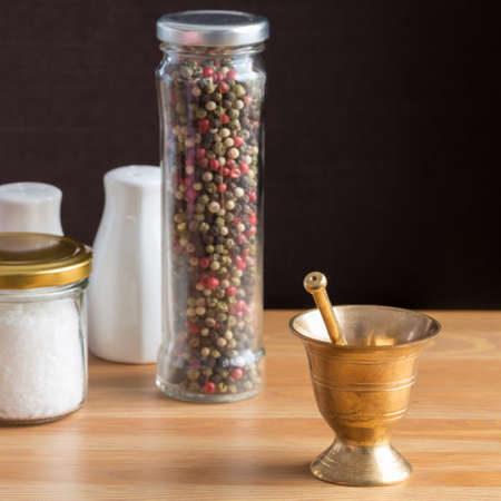pepper castor: Concept of salt and pepper accessories. Mortar, jars with salt and pepper, porcelain salt and pepper on wooden background. Square