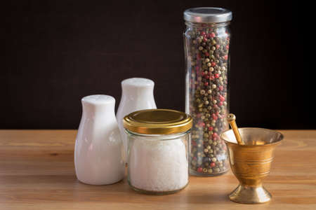 pepper castor: Concept of salt and pepper accessories. Mortar, jars with salt and pepper, porcelain salt and pepper on wooden background. Horizontal