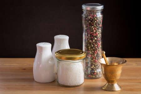 sal: Concepto de accesorios de sal y pimienta. Mortero, tarros con sal y pimienta, la sal y la pimienta de la porcelana en el fondo de madera. Horizontal Foto de archivo