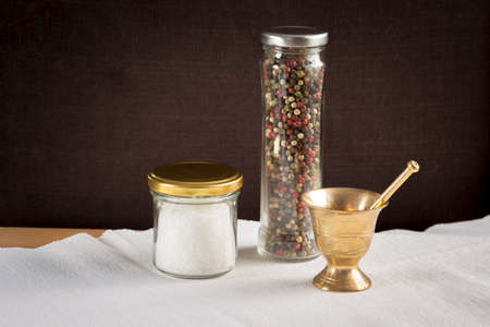 pepper castor: Concept of salt and pepper accessories. Mortar, jars with salt and pepper on white napkin