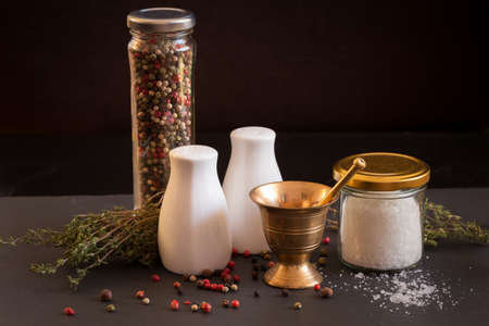 Concept of salt and pepper accessories. Mortar, jars with salt and pepper, dried thyme, porcelain salt and pepper on black stone background. Horizontal Stock Photo