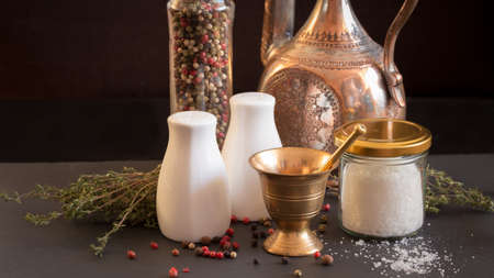 pepper castor: Concept of salt and pepper accessories. Mortar, jars with salt and pepper, old copper jar, dried thyme, porcelain salt and pepper on black stone background. Horizontal, wide screen format Stock Photo