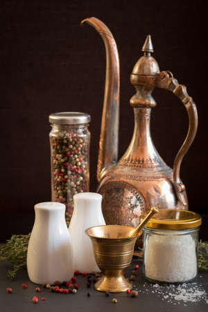 pepper castor: Concept of salt and pepper accessories. Mortar, jars with salt and pepper, old copper jar, dried thyme, porcelain salt and pepper on black stone background. Vertical