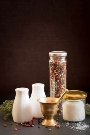 Concept of salt and pepper accessories. Mortar, jars with salt and pepper, dried thyme, porcelain salt and pepper on black stone background. Vertical
