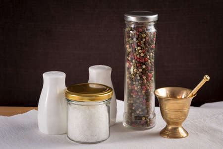 pepper castor: Concept of salt and pepper accessories. Mortar, jars with salt and pepper, porcelain salt and pepper  on white napkin