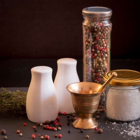 pepper castor: Concept of salt and pepper accessories. Mortar, jars with salt and pepper, dried thyme, porcelain salt and pepper on black stone background. Square Stock Photo