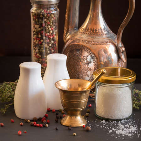 pepper castor: Concept of salt and pepper accessories. Mortar, jars with salt and pepper, old copper jar, dried thyme, porcelain salt and pepper on black stone background. Square