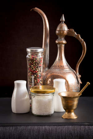 Concept of salt and pepper accessories. Mortar, jars with salt and pepper, old copper jar, porcelain salt and pepper on black stone background. Vertical Stock Photo