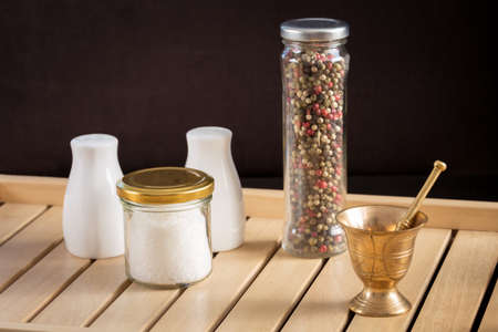 pepper castor: Concept of salt and pepper accessories. Mortar, jars with salt and pepper, porcelain salt and pepper on wooden tray Stock Photo