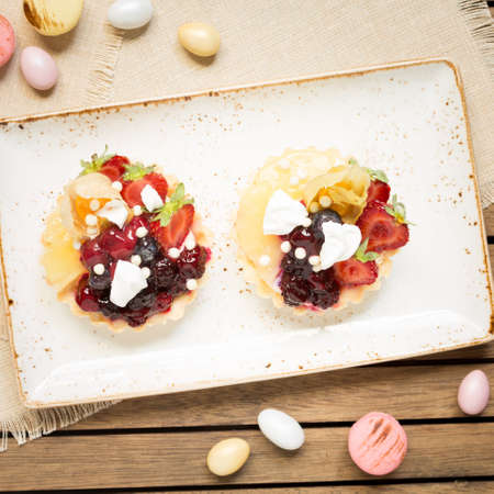 warm color: Fruit tarts and macaroons on a wooden background. Top view, square, warm color