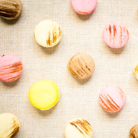 warm color: Macaroons with yellow macaroon on a linen napkin. Top view, square, warm color