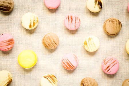 warm color: Macaroons with yellow macaroon on a linen napkin. Top view, horizontal, warm color