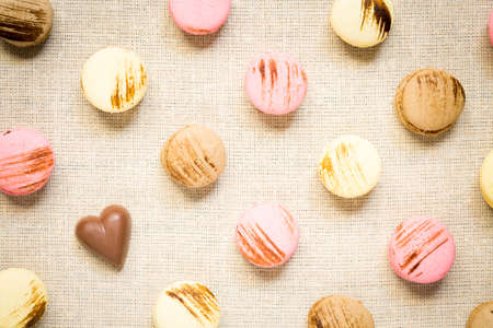 warm color: Macaroons with chocolate heart on a linen napkin. Top view, horizontal, warm color Stock Photo