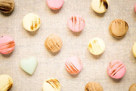 warm color: Macaroons with pistashio chocolate heart on a linen napkin. Top view, horizontal, warm color