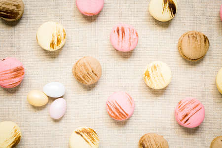 warm color: Macaroons with sweet eggs on a linen napkin. Top view, horizontal, warm color Stock Photo