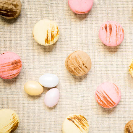 warm color: Macaroons with sweet eggs on a linen napkin. Top view, square, warm color Stock Photo