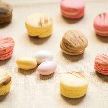 warm color: Macaroons with sweet eggs on a linen napkin. Square, warm color