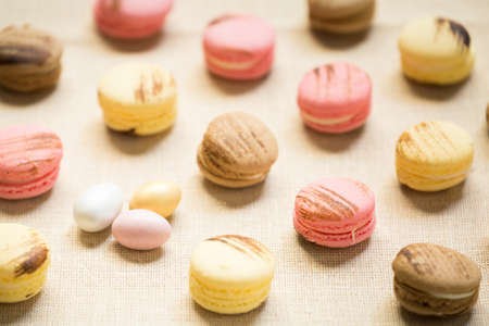 warm color: Macaroons with sweet eggs on a linen napkin. Horizontal, warm color Stock Photo