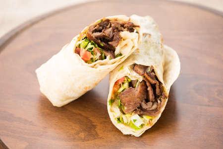 Doner kebab on wooden background. Natural light, horizontal Фото со стока