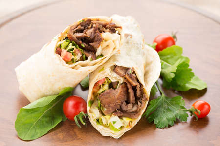 Doner kebab with cherry tomatoes and salad on wooden background. Natural light, horizontal
