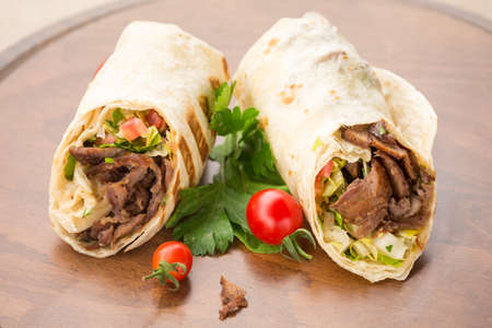 Doner kebab on wooden background with tomatoes and greens. Natural light, horizontal Фото со стока - 41989106
