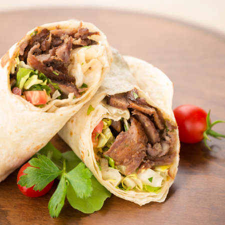 Doner kebab on wooden background with tomatoes and greens. Natural light, square Фото со стока