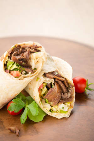 Doner kebab on wooden background with tomatoes and greens. Natural light, vertical