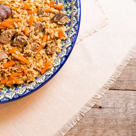 Pilaf in the handmade plate on the wooden background. Square Reklamní fotografie